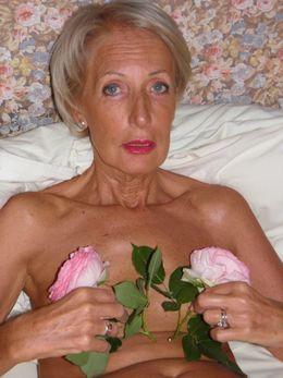 Elegant slim granny posing naked in..