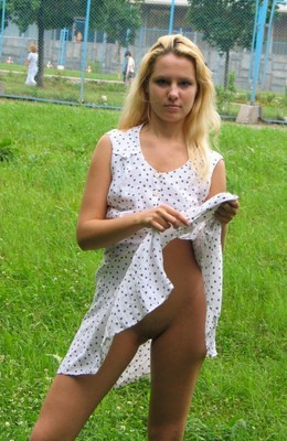Blonde nude on green grass in public..