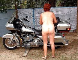 The wife of a biker posing on a..